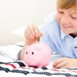 Cute boy putting a coin in a piggybank at home